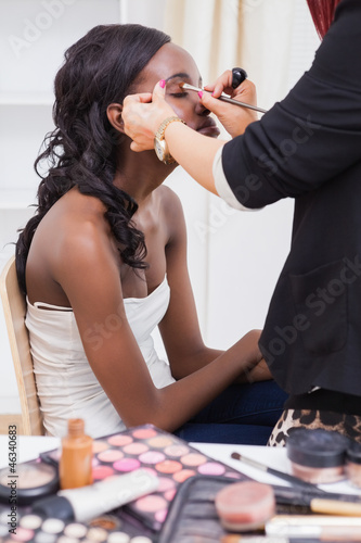 Woman sitting while getting makeup done
