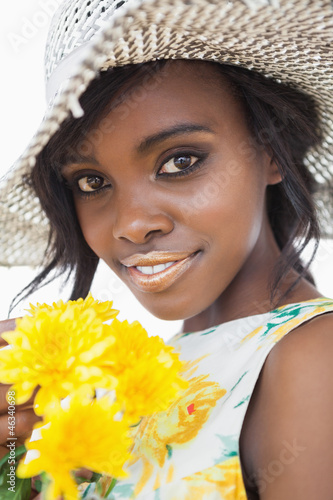Woman wearing hat and holding flowers