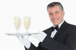 Waiter holding tray with glasses full of champagne