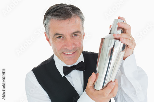 Smiling waiter shaking drink in cocktail shaker