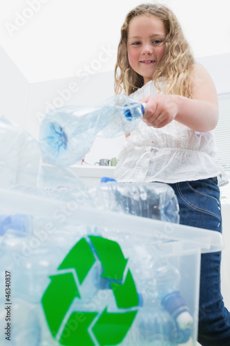Girl throwing bottles into recycling box