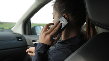 Beautiful businesswoman talking on the phone in car