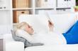 entspannte frau liegt mit tablet auf dem sofa