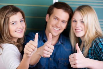 drei lachende schüler zeigen daumen hoch