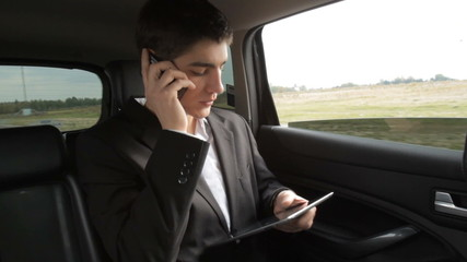 Young businessman working with tablet on the back seat of car