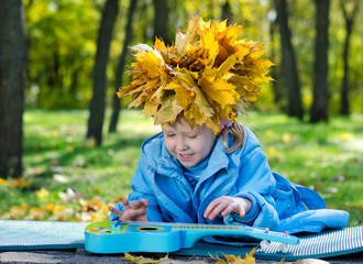 Little girl with a hat of yellow autumn leaves