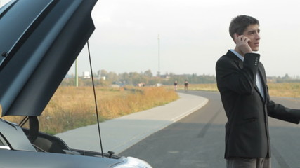 nervous businessman talking on the phone next to broken car