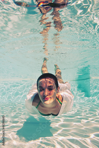 Underwater woman portrait with green bikini in swimming pool.