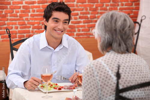 Grandmother and grandson having meal in restaurant