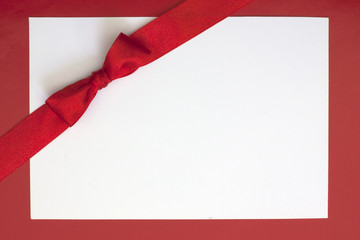 Christmas sheet of paper and red ribbon gift background