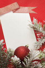 Christmas sheet of paper and baubles on red background