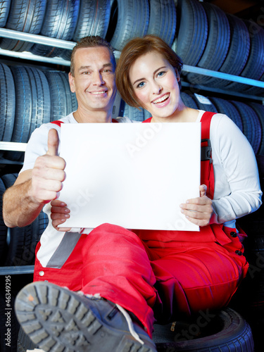 Two car mechanics showing blackboard and thumb up