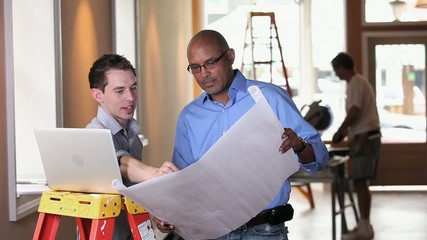 Architect and small business owner discussing blueprint and using laptop inside building under construction