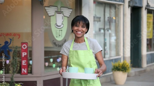 Proud African American coffee shop owner in apron holding tray with coffee cups outside cafe