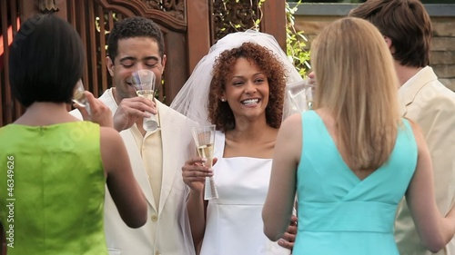 Smiling bride and groom toasting and drinking champagne with friends at wedding reception