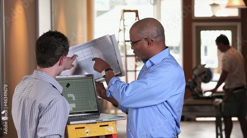 Architect and small business owner discussing plans and using laptop inside building under construction