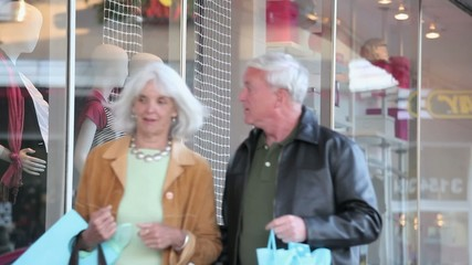 Smiling Caucasian couple window shopping