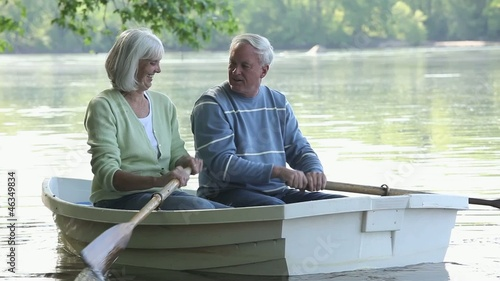Smiling Caucasian couple rowing boat on river
