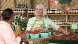 Woman purchasing basket of fresh strawberries from worker at farmer's market