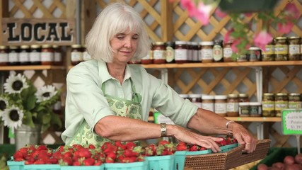 Smiling senior Caucasian woman stocking baskets of fresh strawberries at farmer's market and looking at camera while taking a bite from a strawberry