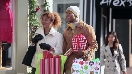 Couple in warm clothing Christmas window shopping on urban street