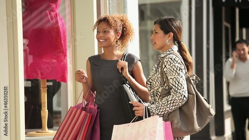 Women with shopping bags entering shop on urban street