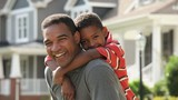 Smiling Black father and son hugging and looking at camera in front yard of suburban house
