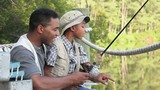 Black father and son fishing