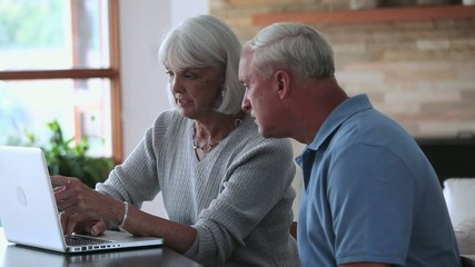 Senior Caucasian couple using laptop and talking