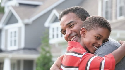 Smiling Black father and son hugging
