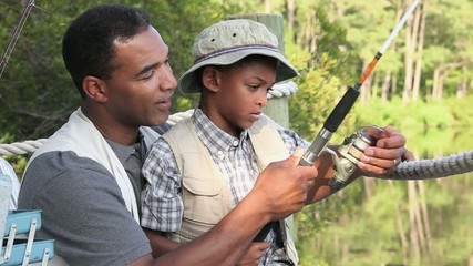 Black father and son adjusting reel on fishing rod