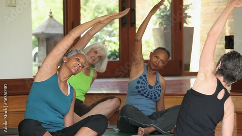 Group of mature women stretching on mats in yoga class