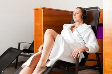 Junge Frau entspannt in Spa mit Musik
