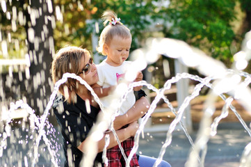 mother and daughter playing with fountain