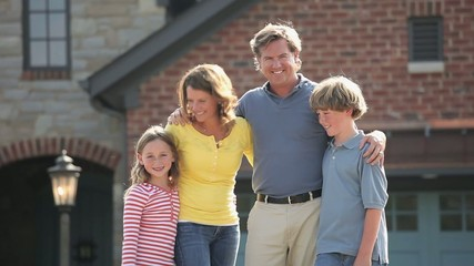 Smiling Caucasian family hugging in front of house