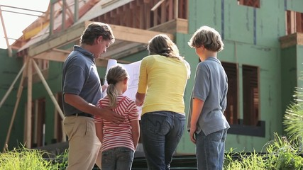 Caucasian family looking at blueprints outside house under construction