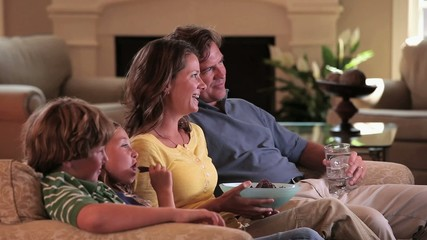 Caucasian family watching TV  on sofa in living room