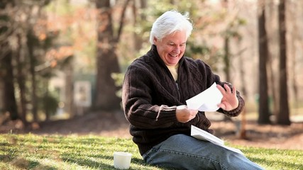 Smiling senior Caucasian man receiving good news in mail and showing paper to camera