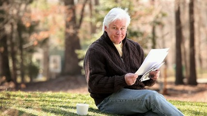 Senior Caucasian man sitting on lawn and reading paperwork
