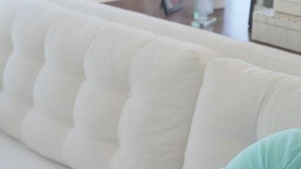 Caucasian mother breastfeeding baby on sofa