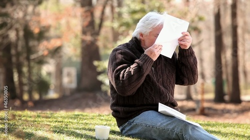 Senior Caucasian man sitting in grass and receiving good news in mail