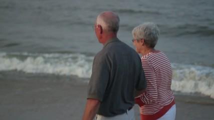 Senior Caucasian couple walking on beach