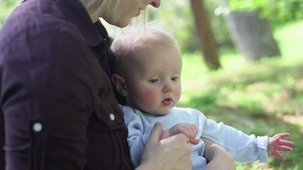 Caucasian mother holding baby in park