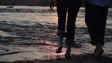 Caucasian couple walking on riverbank at sunset