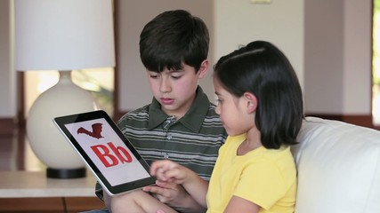 Young boy and girl on sofa using digital tablet to practice alphabet