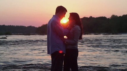 Caucasian couple hugging and kissing on riverbank at sunset