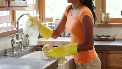 Hispanic woman cleaning the sink in her kitchen