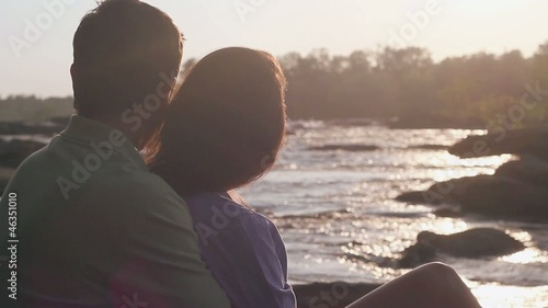 Caucasian couple hugging and kissing on riverbank at dusk