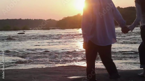 Caucasian couple holding hands and hugging on riverbank at sunset