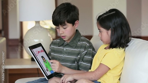 Young boy and girl on sofa using digital tablet to read Spanish language book
